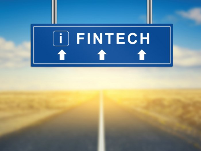 fintech words on blue road sign with blurred background